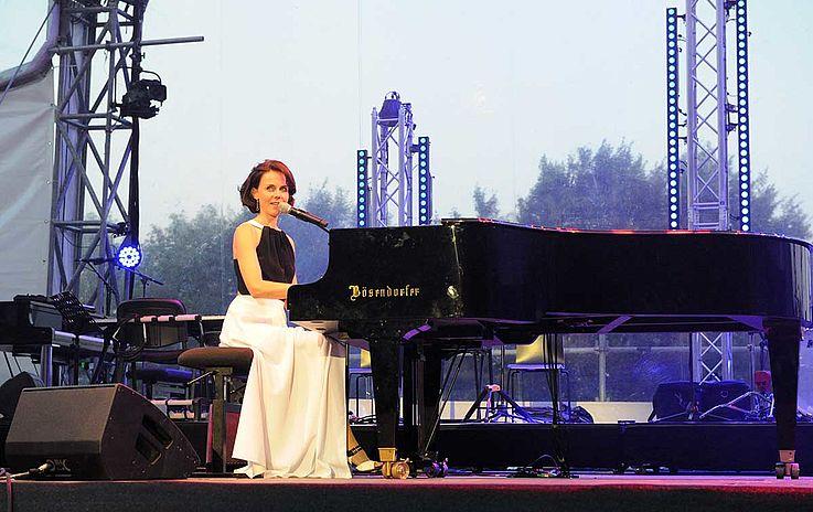 Elegante junge Dame an einem entsprechend eleganten Flügel von Bösendorfer auf der Bühne.