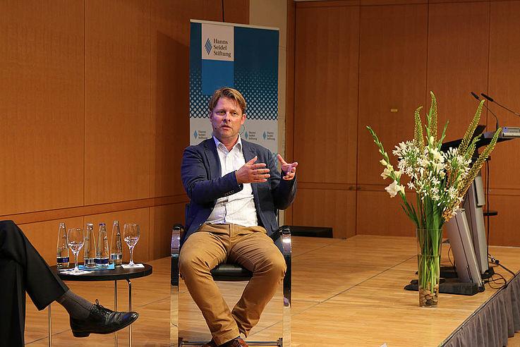 Steinberg, ein jüngerer Mann auf dem Podium gestikulierend, erklärend.