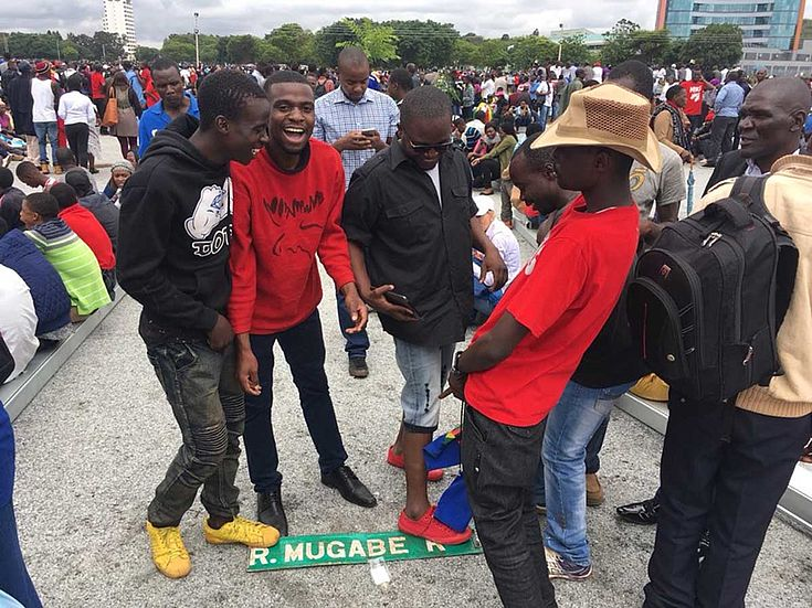 Junge Demonstranten treten auf ein Straßenschild mit Mugabes Namen und freuen sich.