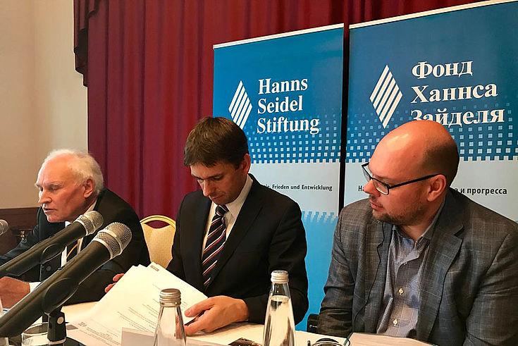 Drei Herren kramen in Unterlagen während einer Konferenz. In der Mitte unser Verbindungsstellenleiter für Moskau, Jan Dresel.