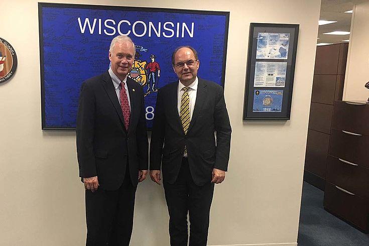 """Schmidt und Johnson vor einem Bild auf dem """"Wisconsin"""" geschrieben steht"""