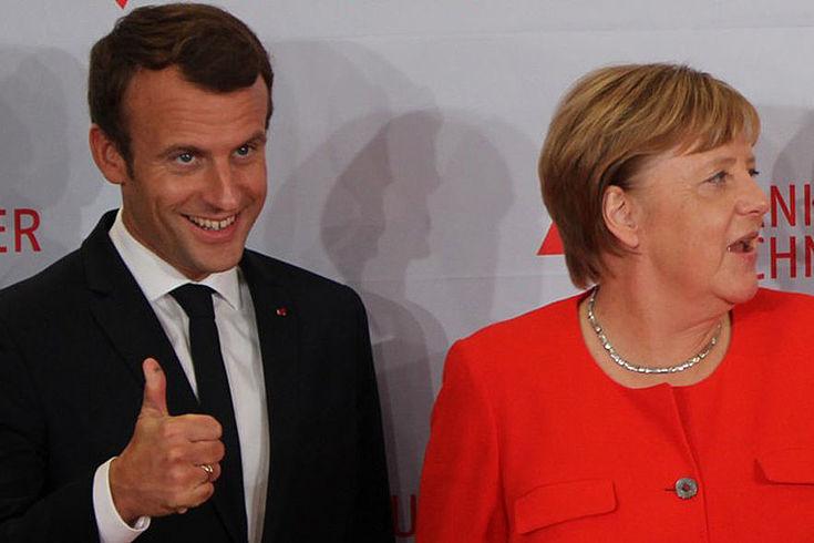 Macron (links) steht neben Angela Merkel und freut sich. Merkel ruft gerade etwas nach links.