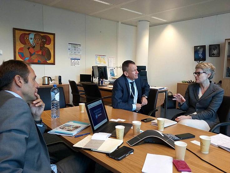 Gespräch an einem Büro. Zwei Männer in formalen Anzügen hören einer smart gekleideten Dame zu, die gerade etwas erklärt.