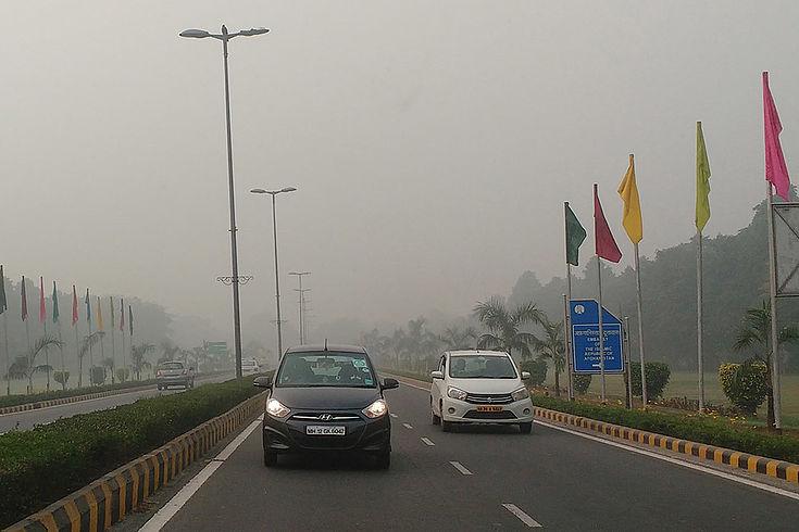 Breite Stadtstraße in Delhi mit Flaggen am rechten Rand, wo der Präsidentenpalast im dichten Smog nicht zu erkennen ist. Autos verschwinden im Dunst.