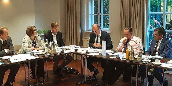 Konferenzraum mit Konferenztisch über Eck mit einigen Experten und einer Expertin beim Informationsaustausch