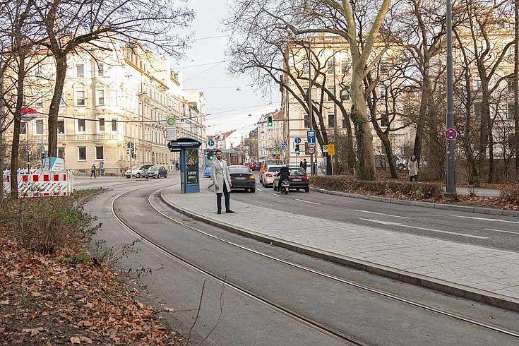 Von Weitem ist ein Mann zu sehen, der auf einer Verkehrsinsel zwischen Trambahnhaltestelle und einer Straße steht.