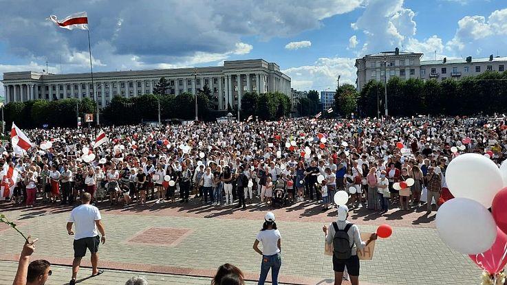 Ein weiter Platz voller Demonstranten, Flaggen, Fahnen, gutes Wetter