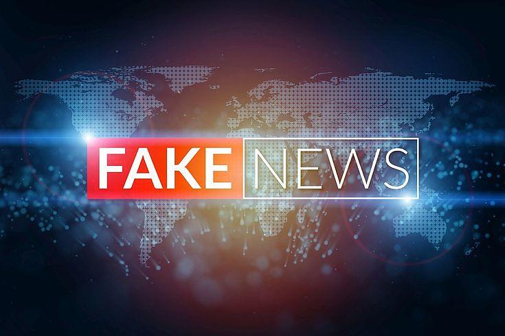 """Eine Weltkarte mit der großen Überschrift """"FAKE NEWS"""""""