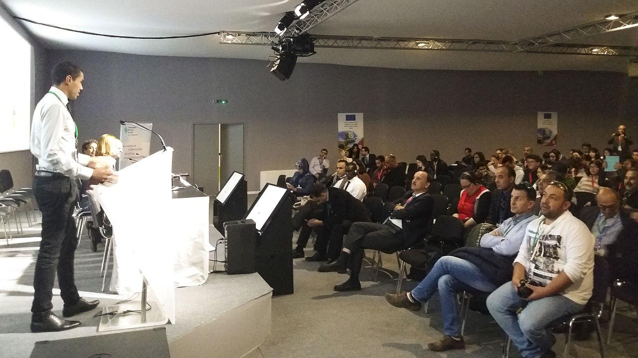 Ein Redner präsentiert vor einem Publikum Ergebnisse