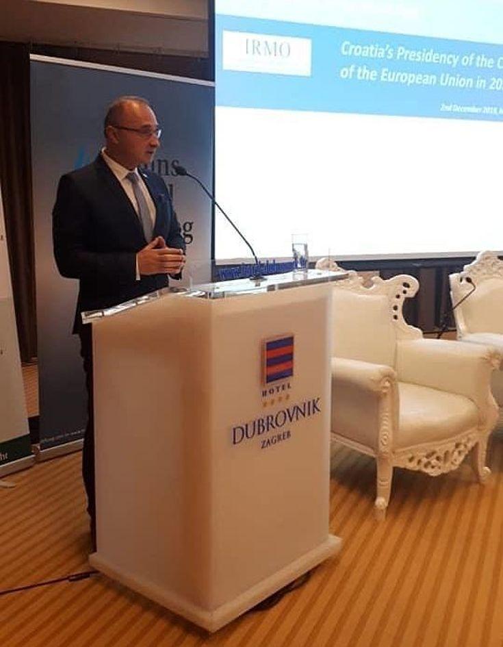 Mann im Anzug an einem Rednerpult mit dem Emblem Kroatiens.