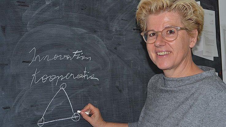 Frau Kapeller, Kurzhaarschnit, sportliche Brille, an einer Tafel zeichnend. Lächelt in die Kamera.