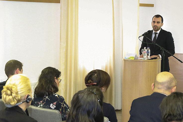Begrüßung der Konferenzteilnehmer durch István Joó an Redepult