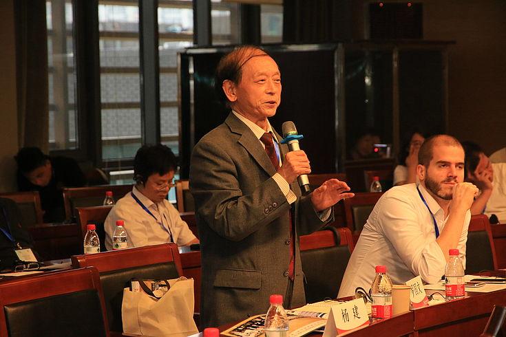 Chinesischer Diplomat steht mit Mikro in der Hand und redet