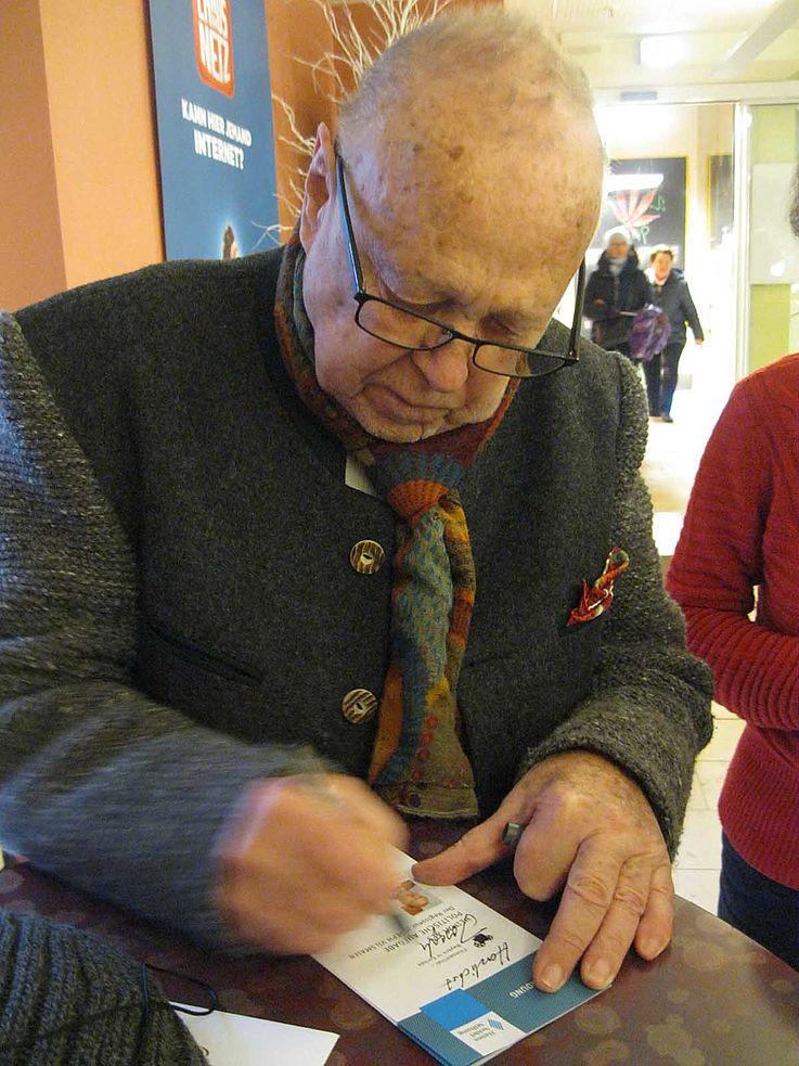 Vilsmaier schreibt ein Autogramm auf das Programm einer HSS-Veranstaltung