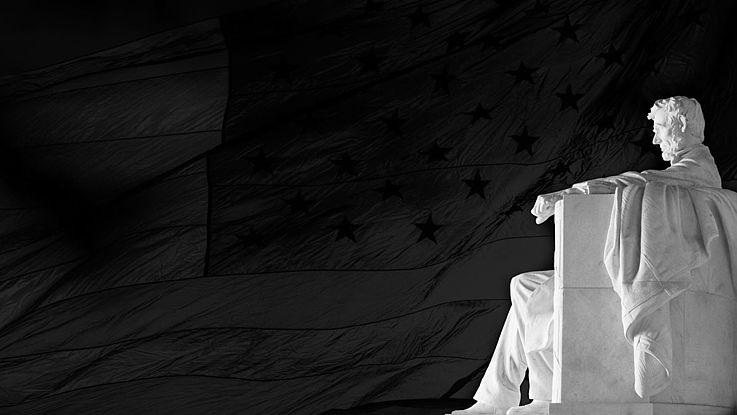 """Die marmorne Statue Lincolns im washingtoner """"Lincoln Memorial"""" im Profil aufgenommen. Er sitzt auf einem Sessel, die Hände auf den Armlehnen und blickt würdig."""