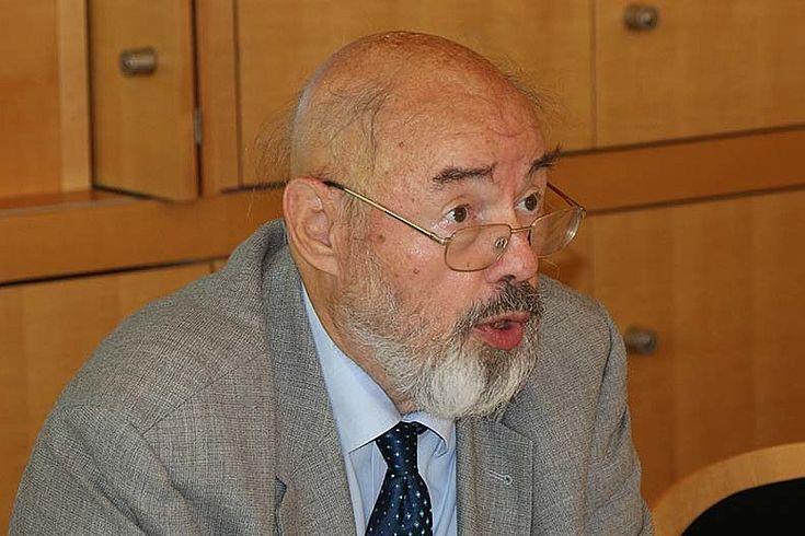 Alter Professor, weißer Bart, Brille, Glatze, eindringlicher Blick, erklärt