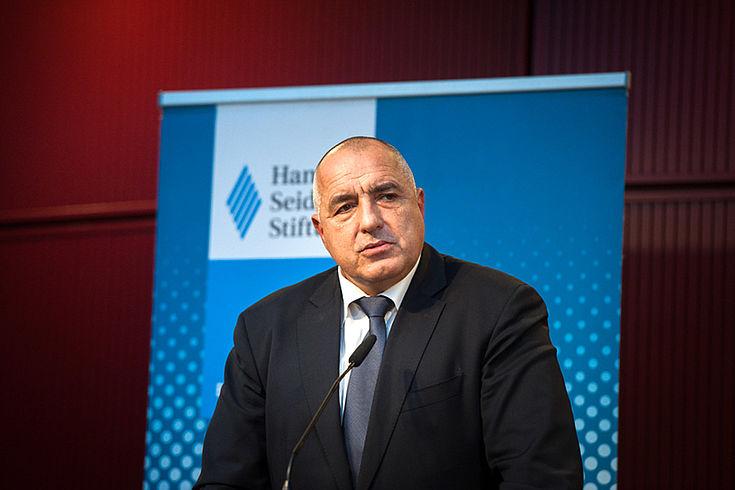 Grimmig dreinblickender, beleibter, älterer Mann in gut sitzendem dunklen Anzug am Rednerpult. Im Hintergrund eine HSS-Stellwand.
