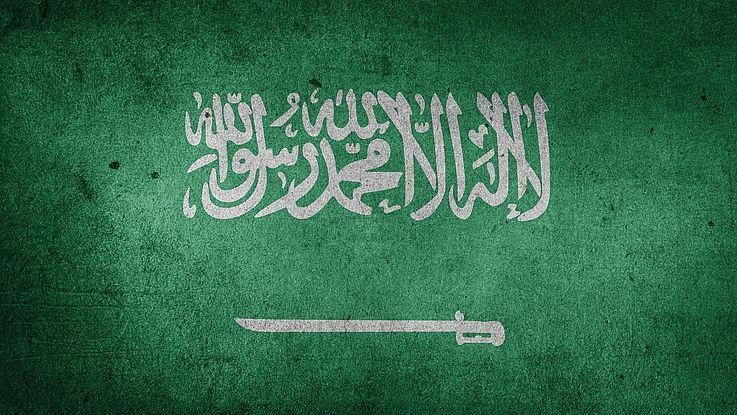 Arabischer Schriftzug mit einem Säbel horizontal darunter. Das Wappen Saudi-Arabiens.