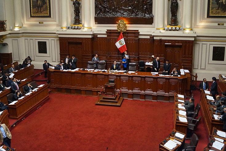 Blick in den peruanischen Kongresssaal mit hufeisenförmig angeordneten Sitzen und rotem Teppich. Vorne die Landesflagge vor einem Podium.