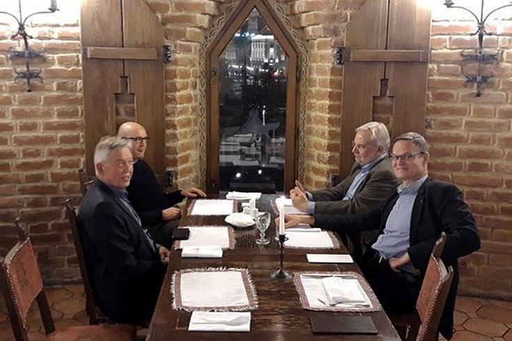 Vier Herren in einem Turmzimmer an einem Tisch vor einem Spitzen Turmfenster. Draußen ist die Moskauer Innenstadt zu sehen.