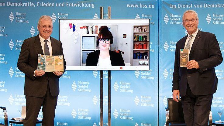 Markus Ferber und Joachim Herrmann halten die Hatespeech Broschüre in den Händen