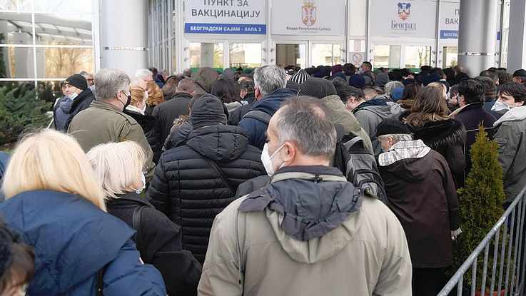 Vor einem Impfzentrum in einer Messehalle von Belgrad bildet sich eine lange Warteschlange.