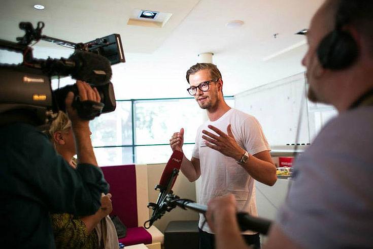 Junger Mann in weißem T-Shirt und mit schwarzer Hornbrille spricht gestenreich vor laufender Kamera, die man im Vordergrund sieht.