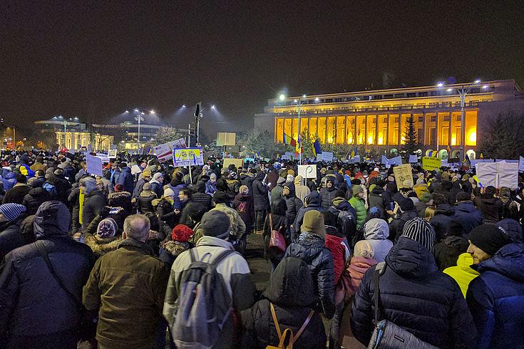Auf der nächtlichen Piata Vikroriei in Bukarest sind viele Menschen versammelt. Manche halten Plakate oder Transparente in die Höhe.