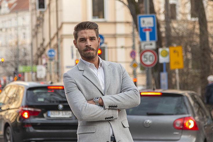Ein junger mann ist vor einer befahrenden Straße zu sehen. Er verschränkt die Arme.