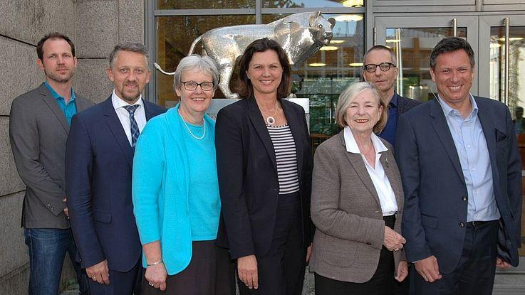 Gruppen von Menschen in seriöser Kleidung vor der Löwenstatue am Eingang des HSS-Konferenzzentrums in München