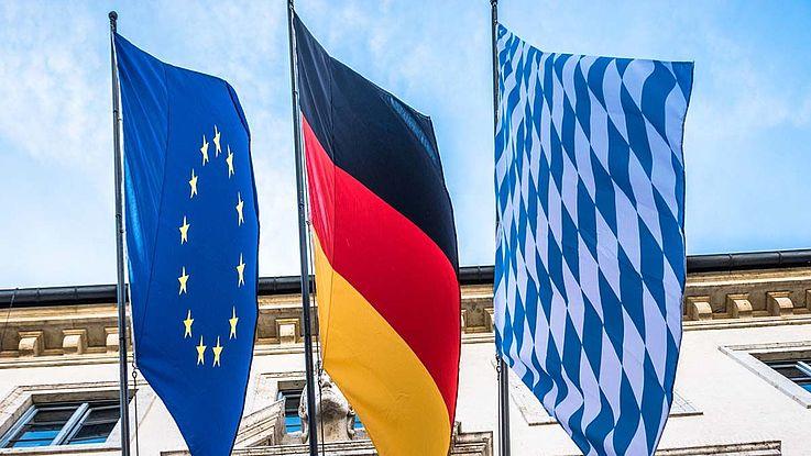 EU-Flagge, Deutschland-Flagge und Bayerische Flagge vor einem alten Gebäude