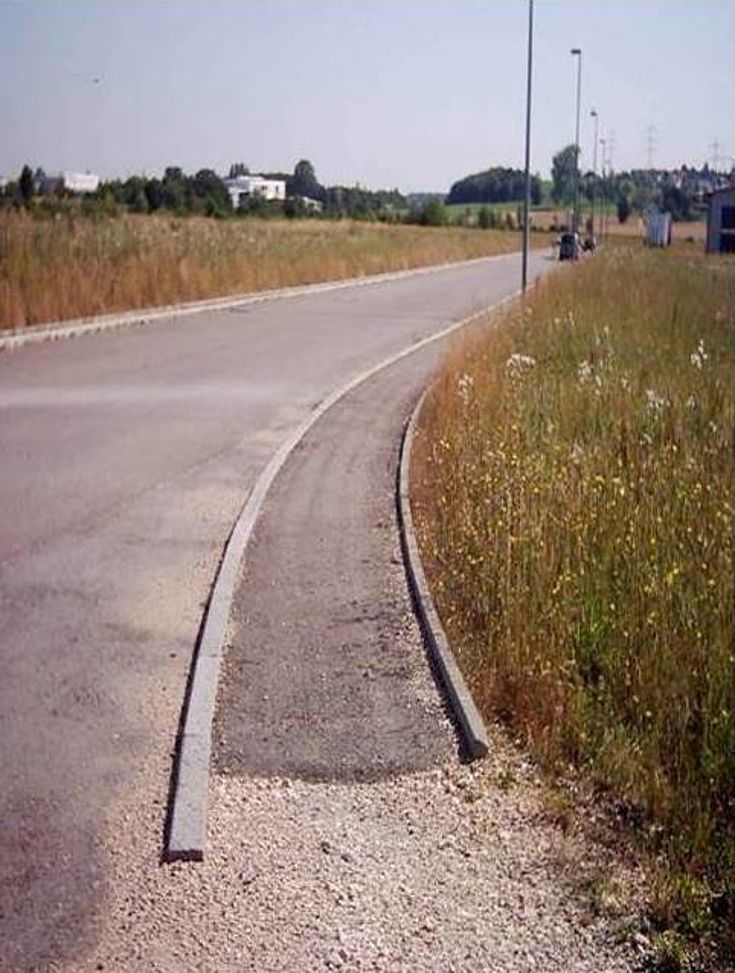 Geteerte Straße verläuft durch eine Wiesenlandschaft. Im Hintergrund sind einzelne Häuser zu sehen.