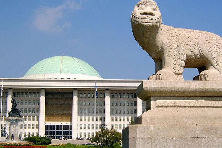 In Seoul steht vor dem niedrigen Parlamentsgebäude mit einer hellen grünen Kuppel eine Steinfigur mit dem Aussehen eines Fabelwesens