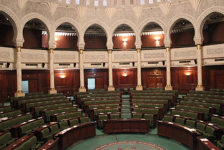 Runder, hoher Saal. Säulen an den Wänden, wertige Holzbänke für die Abgeordneten, ein Rund in der Mitte mit Rednerpult.