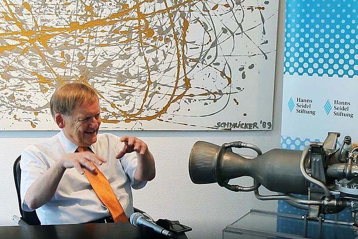 Prof. Schmucker sitzt hinter seinem Schreibtisch, linke Bildseite und gestikuliert. In der Mitte des Bildes steht das Modell eines Raketentriebwerkes vor einer HSS-Stellwand. Rechts am Bildrand sitzt Erich Kornberger in einem karierten Sacko und wartet die Antwort auf eine Frage ab.