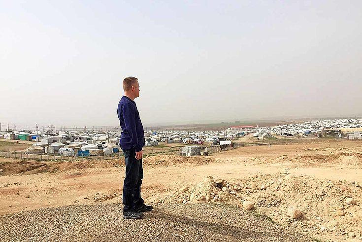 Ein Mann steht auf einem staubigen Hügel in der Wüste. Im Hintergrund die grauen, weißen Siluetten der Zeltstadt.