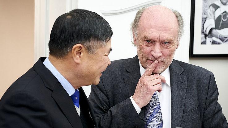 Älterer Herr im grauen Anzug legt sich im Gespräch mit einem der internationalen Gäste, konzentriert einen Finger auf die Lippen, als folge er einem schwierigen Argument.
