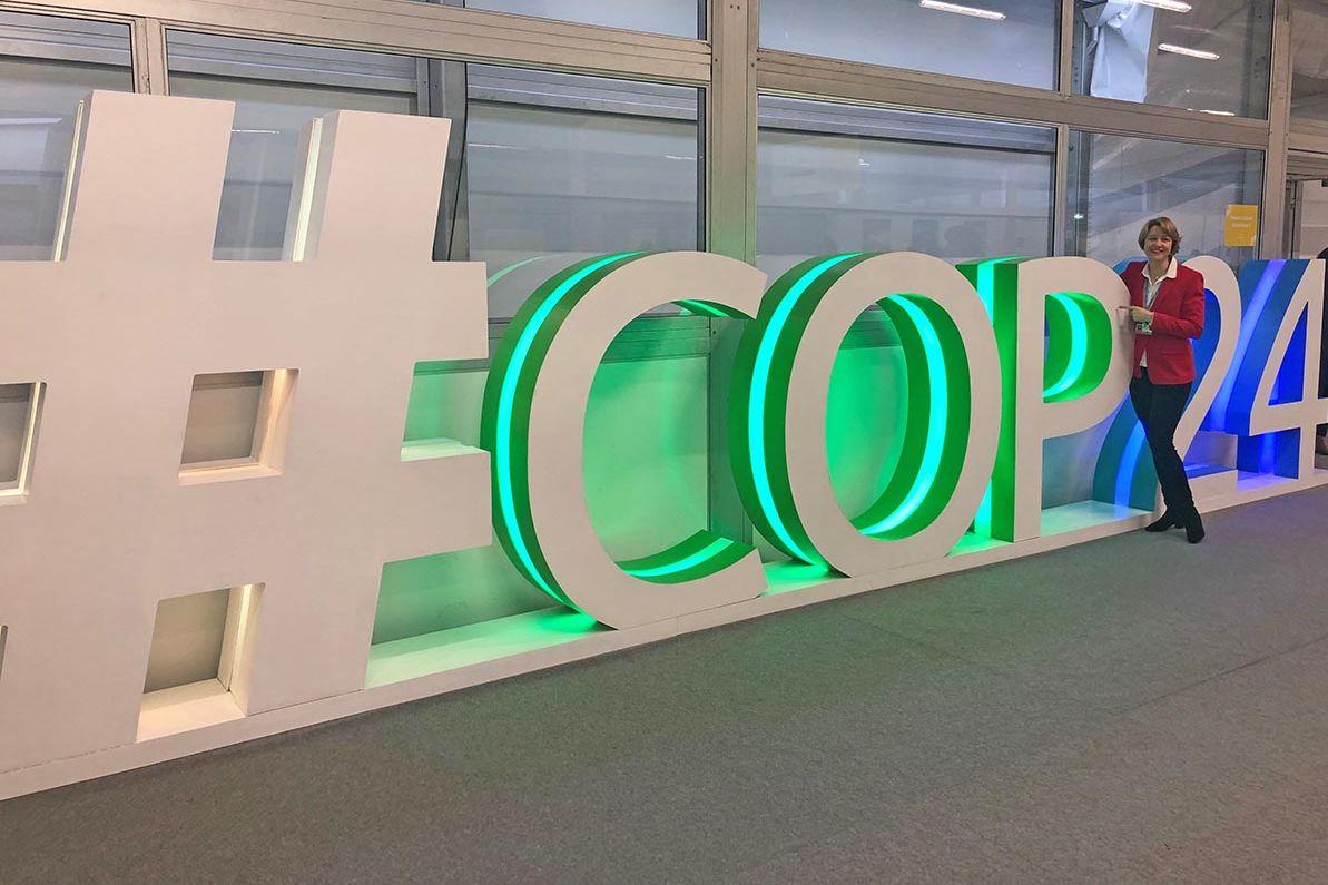 Weisgerber am Ende eines überlebensgroßen, auf dem Boden stehenden Schriftzug: #COP24