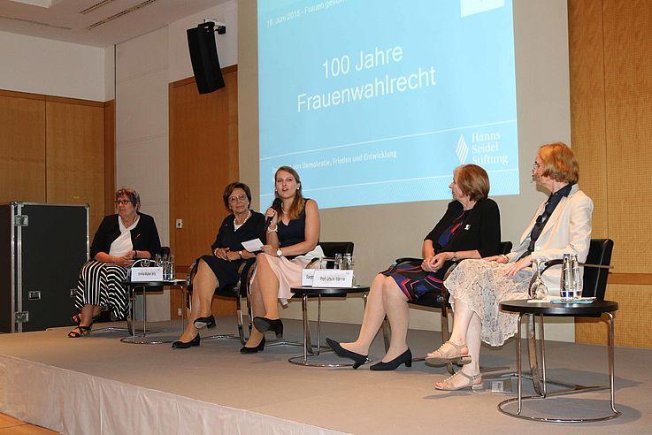 Die vier Damen und die Moderatorin auf dem Panel. Moderatorin hat das Mikro in der Hand und spricht gerade.