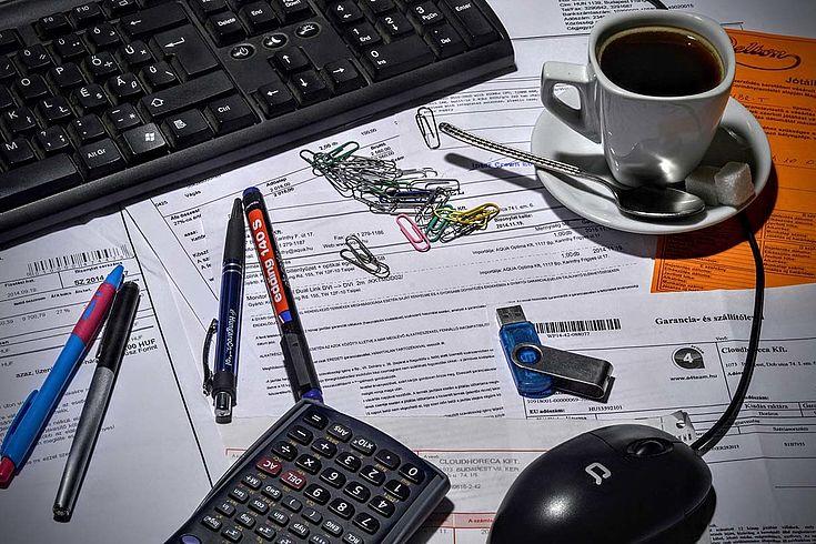 Ein unaufgeräumter Schreibtisch, der bürokratische Verzweiflung symbolisieren soll