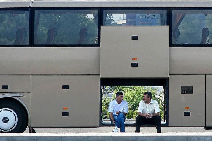 Zwei Männer sitzen in der offenen Gepäcktür eines Reisebusses und reden miteinander.