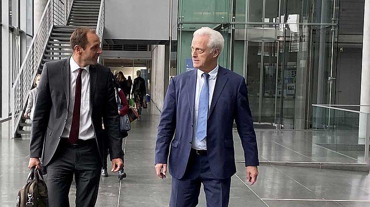 Zwei Männer vor dem Treppenhaus in einem modernen, hohen Raum, gehend, sich unterhaltend