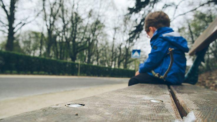 Ein kleiner Junge sitzt traurig auf einer Bank
