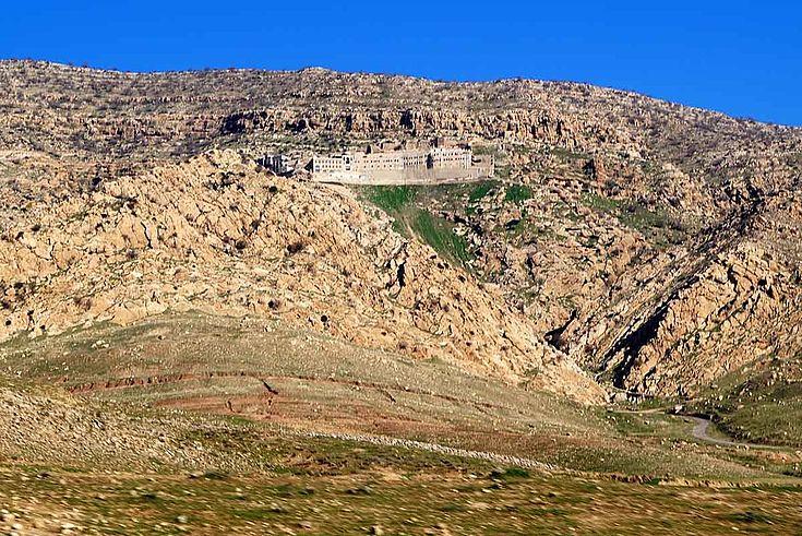 Ein Kloster drückt sich an die steilen Hänge eines staubigen Berges.