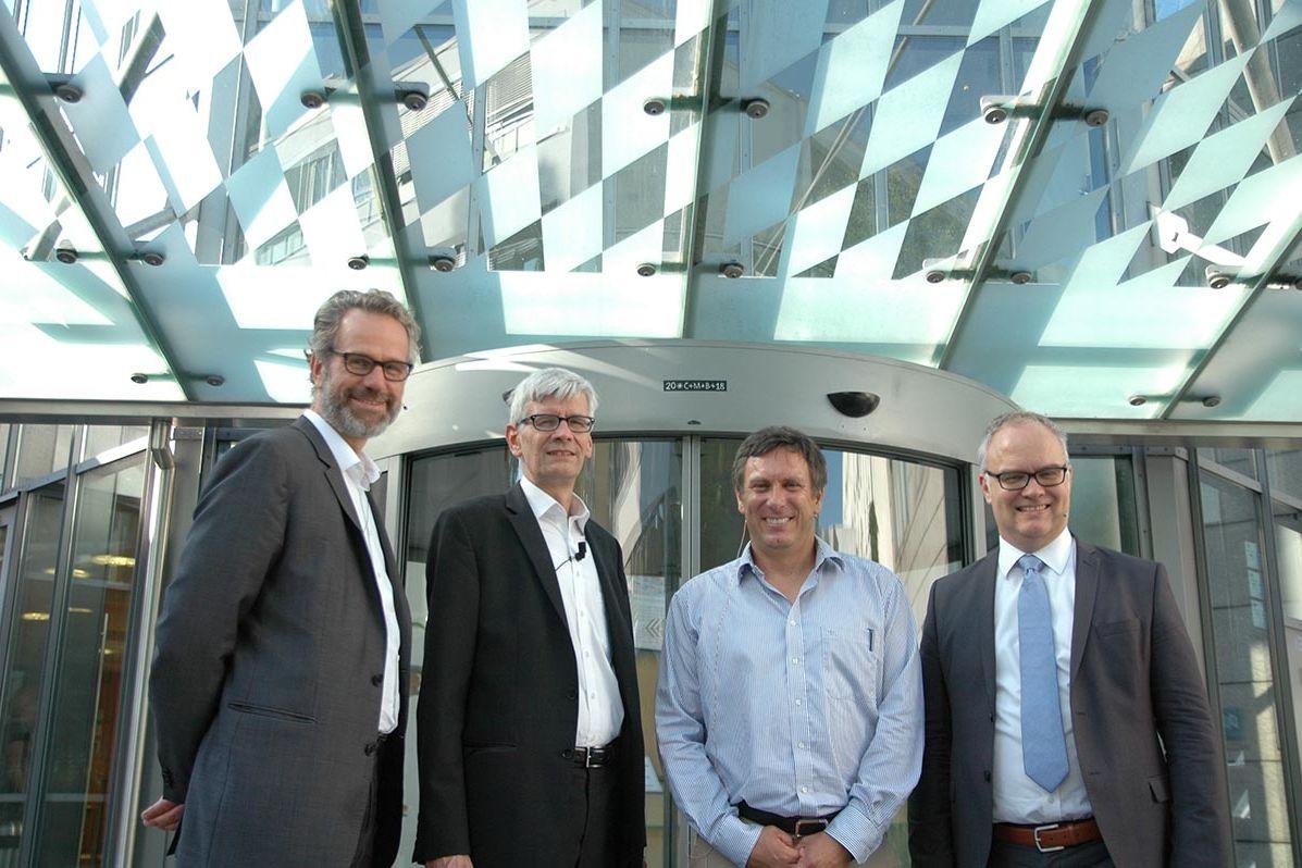 Die vier Herren lächeln in die Kamera vor dem Eingang zum Konferenzzentrum der HSS in München