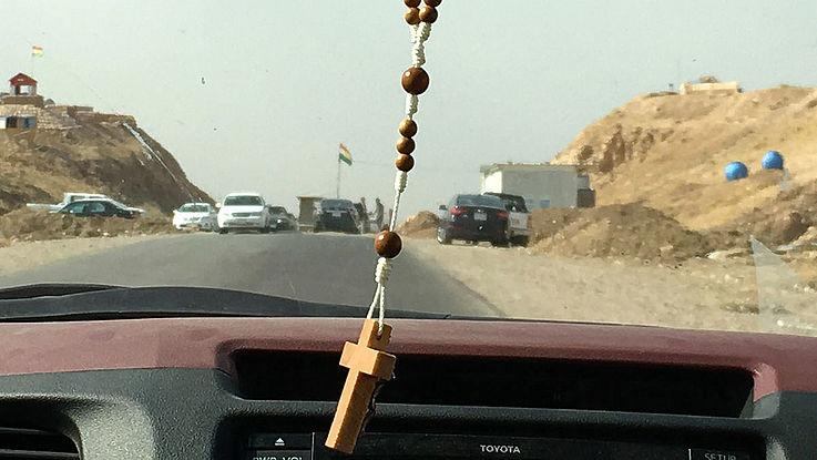 Ein Kreuz hängt von dem Rückspiegel eines Autos, das auf den Checkpoint zufährt.