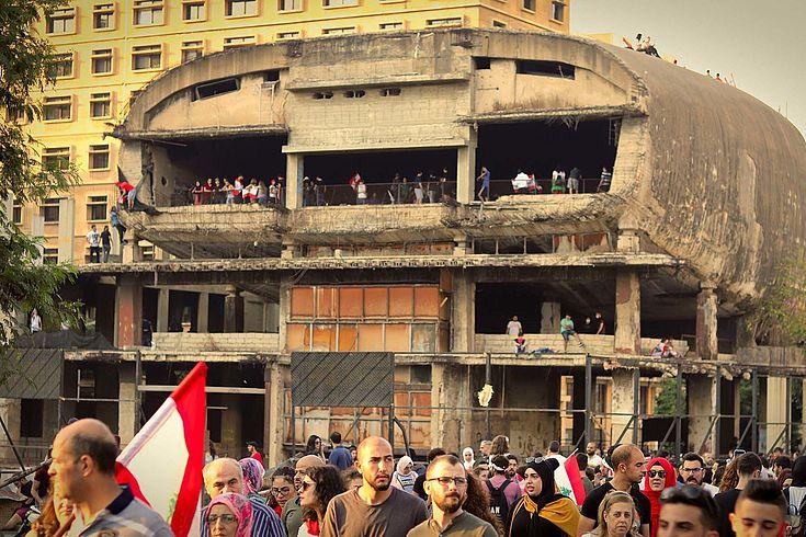 Ein zerstörtes halbrundes Gebäude vor dem Menschen mit der libanesischen Flagge demonsrieren