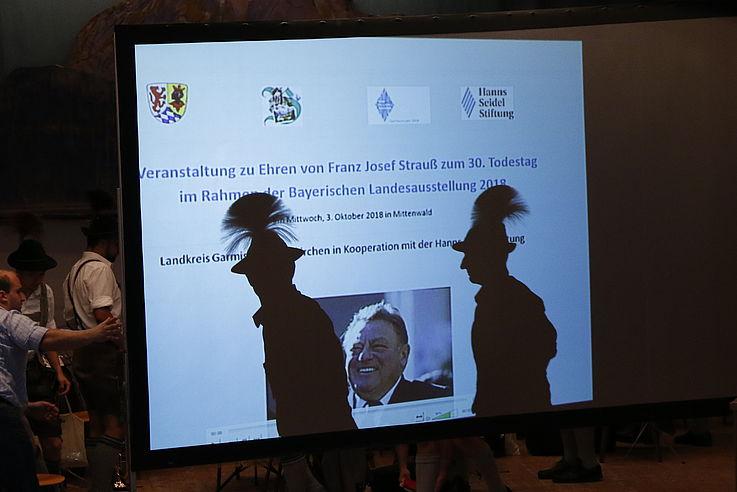 Schatten zweiter Männer mit ihren Hüten hinter einer Power-Point-Folie