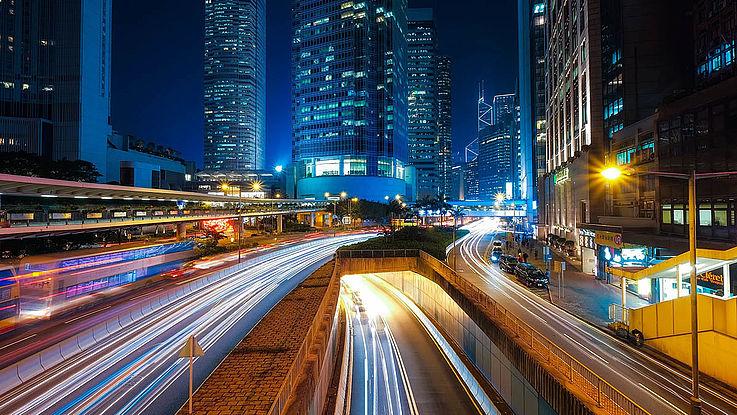 Eine viel befahrene Straße rauscht durch eine hypermoderne Stadt.