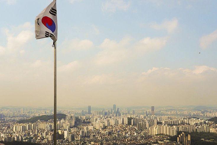 Blick auf das Zentrum von Seoul mit einer Landesfahne im Vordergrund